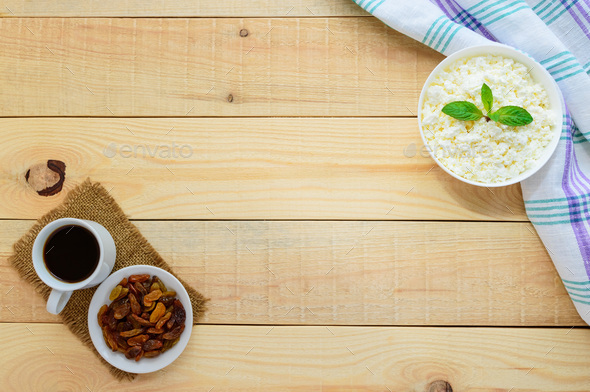Fresh homemade cottage cheese, golden raisins and a cup of coffee. A healthy breakfast. The top view - Stock Photo - Images