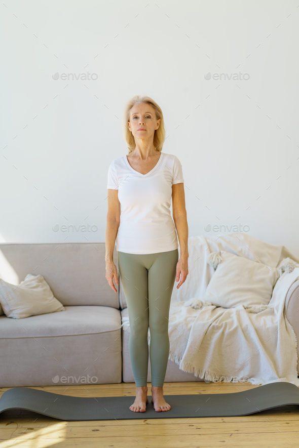 Focused retired mature woman standing standing in mountain pose while doing yoga exercises in living - Stock Photo - Images