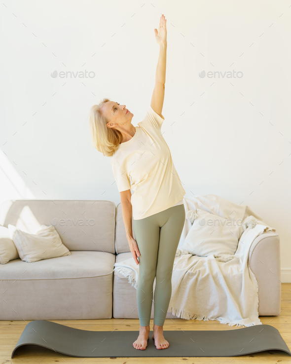 Healthy mature woman standing in yoga pose while exercising in living room at home - Stock Photo - Images