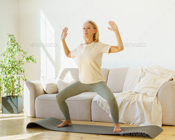 Focused retired mature woman in sportswear practicing yoga asana at home while standing on mat - Stock Photo - Images