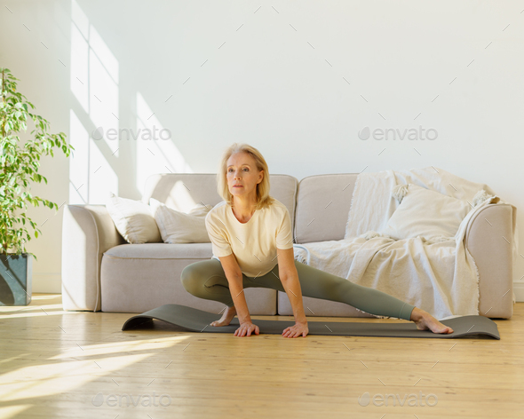 Healthy active retired woman in sportswear doing stretching exercises in on yoga mat in living room - Stock Photo - Images