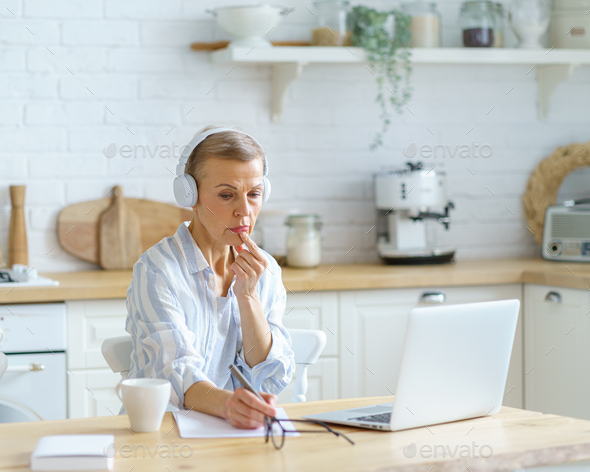 Focused mature woman in headphones sitting in kitchen and making notes, studying online on laptop - Stock Photo - Images