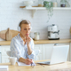 Focused mature woman in headphones sitting in kitchen and making notes, studying online on laptop - PhotoDune Item for Sale