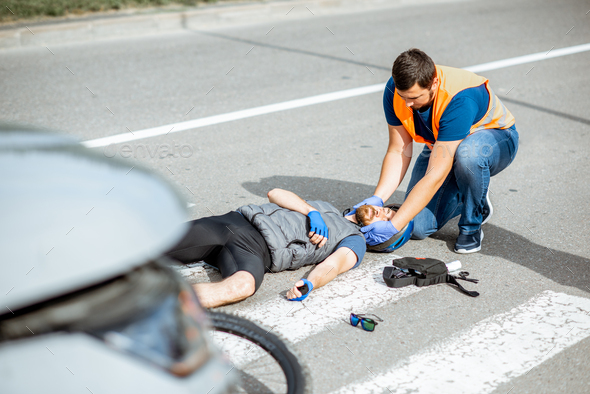 Road accident with injured cyclist and man providing first aid - Stock Photo - Images