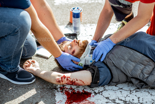 Medics applying emergency care to the injured man on the road - Stock Photo - Images