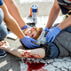 Medics applying emergency care to the injured man on the road - PhotoDune Item for Sale
