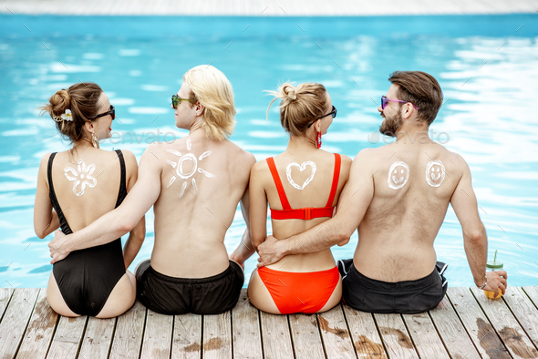 Friends with sun cream on the swimming pool outdoors - Stock Photo - Images