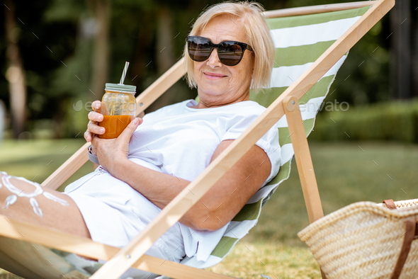 Senior woman on the sunbed outdoors - Stock Photo - Images