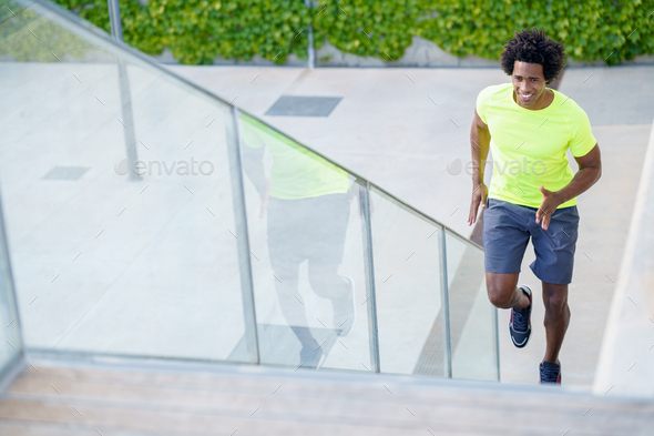 Black man running upstairs outdoors. Young male exercising - Stock Photo - Images