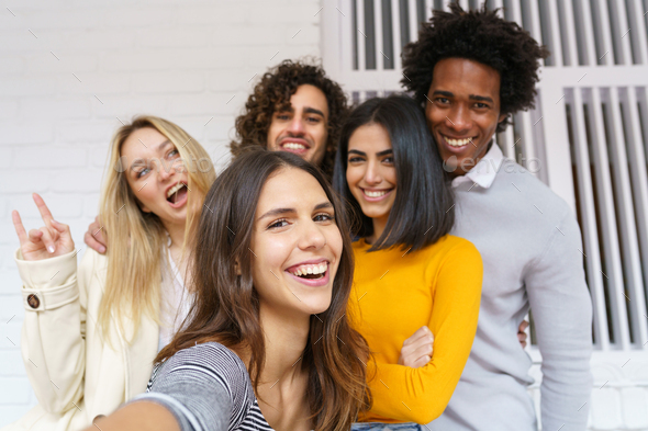 Multi-ethnic group of friends taking a selfie together while having fun outdoors - Stock Photo - Images
