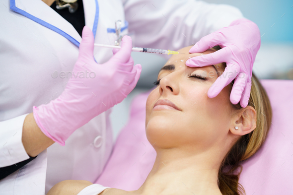Aesthetic doctor injecting botox into the forehead of her middle-aged patient - Stock Photo - Images