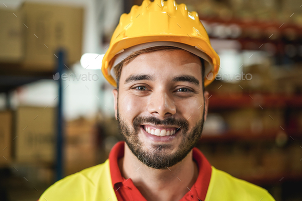 Portrait of man worker smiling on camera inside warehouse - Focus on mouth - Stock Photo - Images