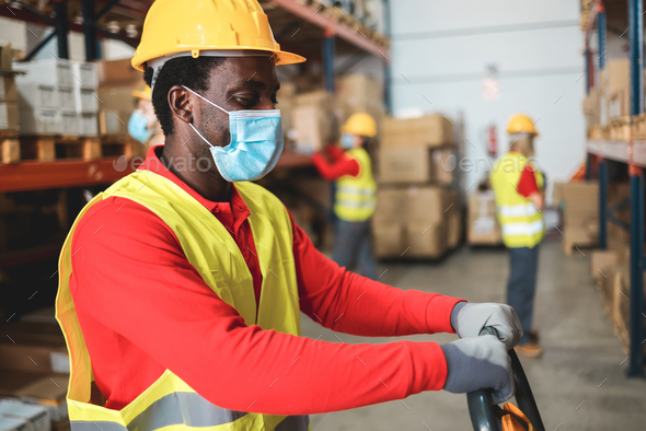 Afro american worker inside warehouse pulling a pallet truck while wearing safety mask - Stock Photo - Images