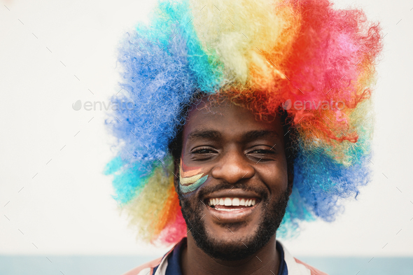 Happy young african man wearing lgbt rainbow flag wig - Focus on face - Stock Photo - Images