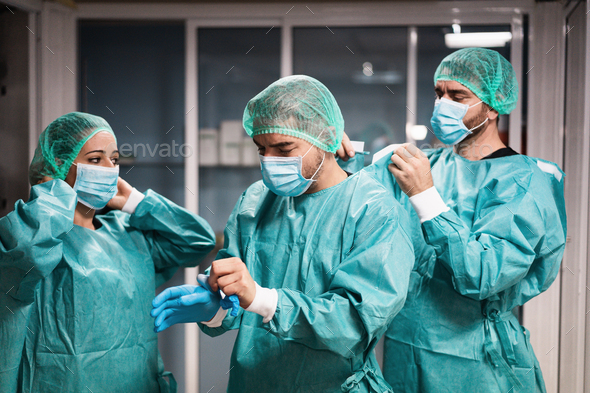 Doctors and nurse preparing to work in hospital for surgical operation during coronavirus outbreak - Stock Photo - Images