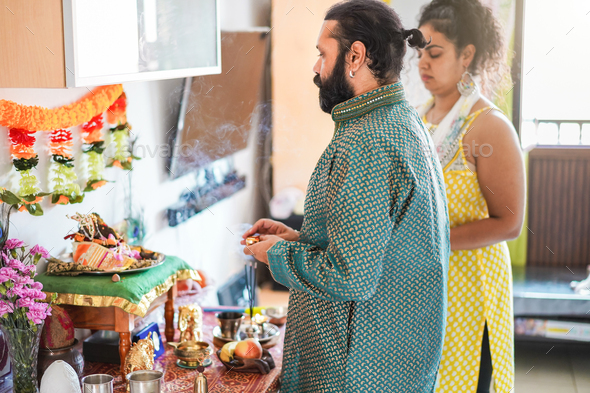 Indian husband and wife celebrating Diwali or hindu festival at home - Focus on man face - Stock Photo - Images