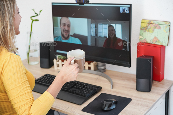 Young woman having an online video call with friends while drinking coffee at home - Focus on cup - Stock Photo - Images