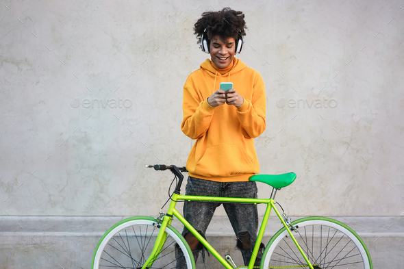 Happy african millennial boy with bike listening music with headphones outdoors - Focus on face app - Stock Photo - Images