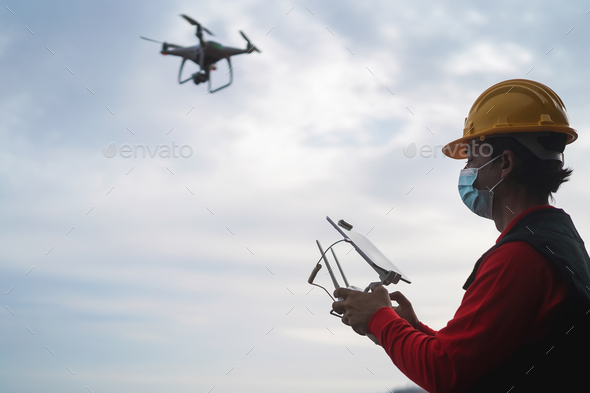 Man engineer flying with drone while wearing safety mask - Focus on right hand - Stock Photo - Images