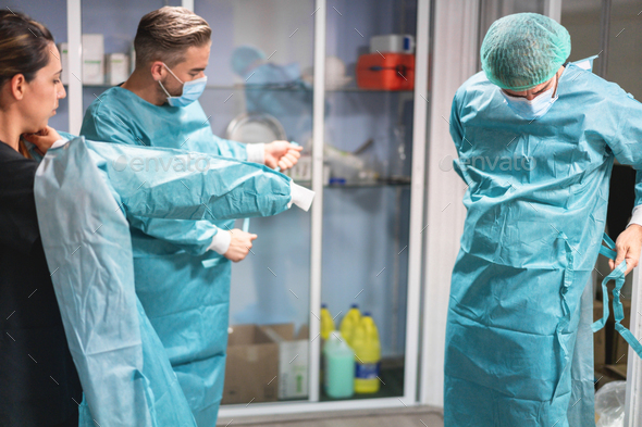 Medical doctors and nurse preparing for surgical operation in hospital during coronavirus outbreak - Stock Photo - Images