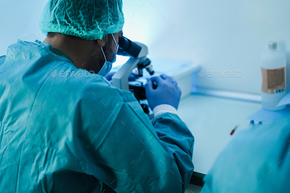 Medical scientists working inside laboratory with microscope - Stock Photo - Images