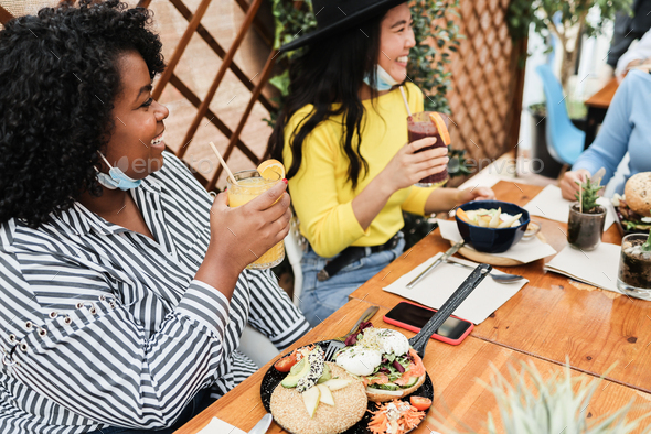 Multiracial young women eating brunch during coronavirus outbreak - Stock Photo - Images