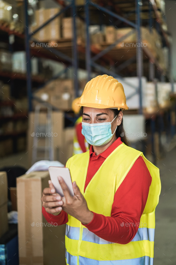 Happy worker women using mobile phone inside warehouse - Focus on face - Stock Photo - Images