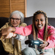 Multiracial senior and young women playing console games at home - Focus on african girl - PhotoDune Item for Sale