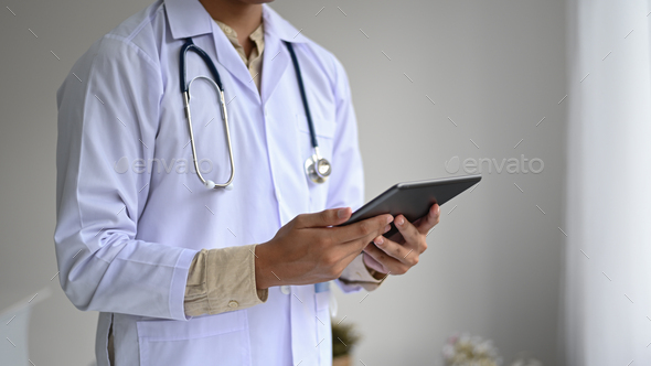Medical professional in a lab gown with a stethoscope holding a tablet in hand, side view shot. - Stock Photo - Images