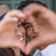 Mixed race couple do hearth sign with hands, looking to camera - love and relationship concept - PhotoDune Item for Sale