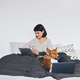 Young woman work on laptop in bed with her dog - PhotoDune Item for Sale