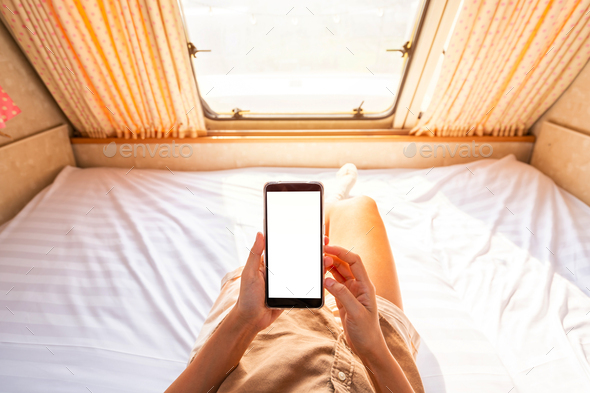 Young woman traveler laying in camper van and using smart phone while road trip traveling - Stock Photo - Images