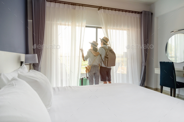 Young couple traveler with luggage looking at view in hotel room on summer vacation - Stock Photo - Images