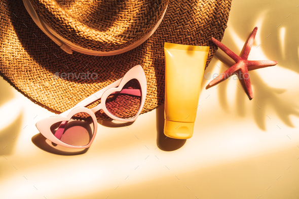 Travel summer accessories and sunscreen with shadow of tropical leaves on color background - Stock Photo - Images