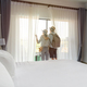 Young couple traveler with luggage looking at view in hotel room on summer vacation - PhotoDune Item for Sale