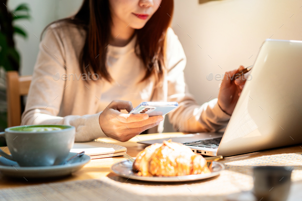 Young woman with cup of coffee using mobile phone and working on laptop at coffee shop - Stock Photo - Images