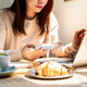 Young woman with cup of coffee using mobile phone and working on laptop at coffee shop - PhotoDune Item for Sale