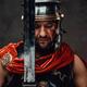 Serious roman warrior posing with sword in dark background - PhotoDune Item for Sale