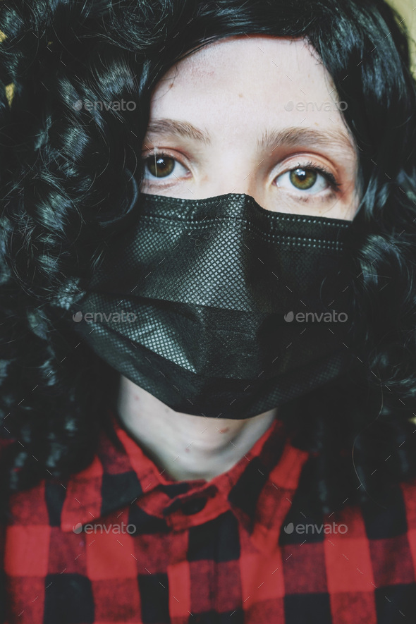 Young woman wearing a black face mask - Stock Photo - Images