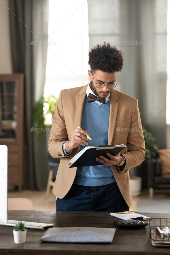 Serious businessman examining work papers - Stock Photo - Images