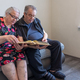An elderly man and woman are looking at pictures in a family photo album. - PhotoDune Item for Sale