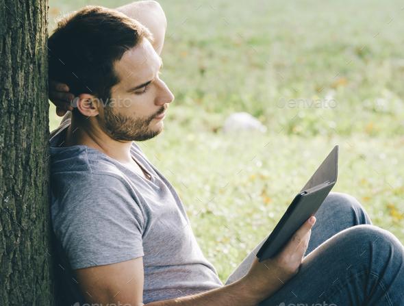 Man reading e book reader - Stock Photo - Images