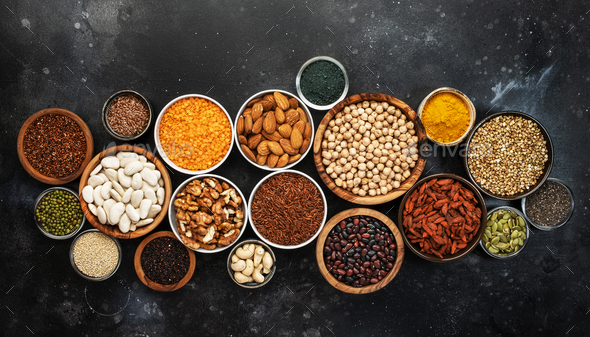 Selection of superfoods, legumes, cereals, nuts, seeds in bowls - Stock Photo - Images