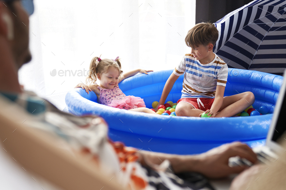 Children sitting in an inflatable ball pool at home - Stock Photo - Images
