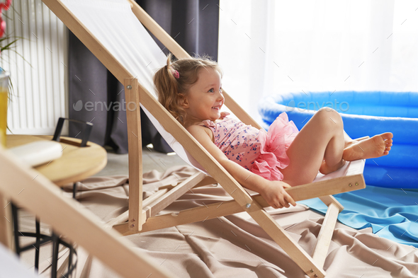 Happy little girl lying outdoor chair in swimwear at home - Stock Photo - Images