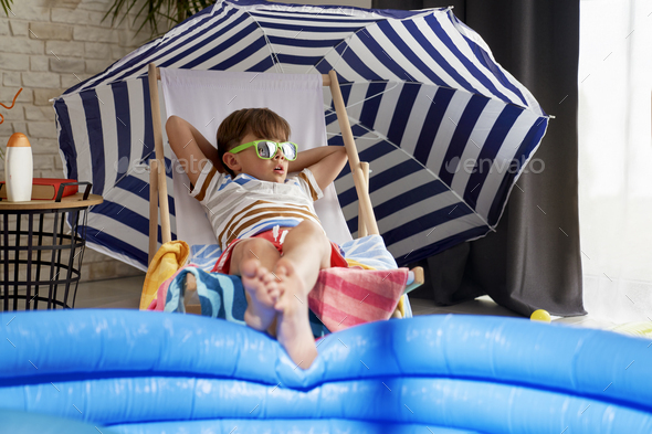 Relaxed boy in sunglasses lying on a chair at home - Stock Photo - Images