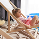Happy little girl lying outdoor chair in swimwear at home - PhotoDune Item for Sale