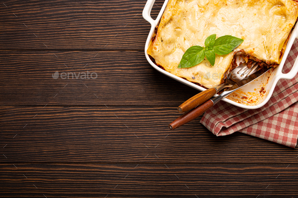 Traditional Italian lasagna in casserole pan on wooden table - Stock Photo - Images