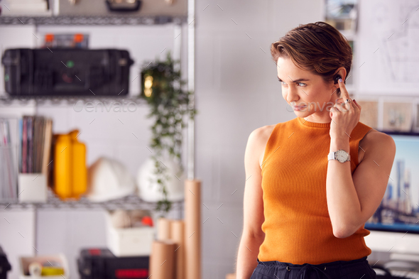 Female Architect In Office Standing At Desk Taking Phone Call On Wireless Earpiece - Stock Photo - Images