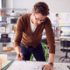 Male Architect Standing At Desk In Office Amending Building Plans - PhotoDune Item for Sale